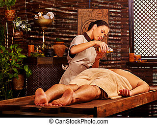 Man having Ayurvedic spa treatment - Man lays her head to...