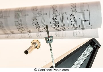 Metronome and mouthpiece of a trumpet isolated on a blank...
