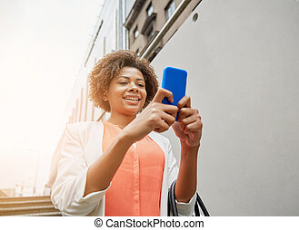 happy african woman with smartphone in city - business,...