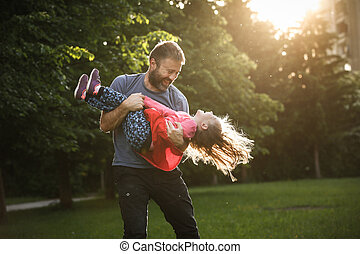Devoted father spinning his daughter in circles, bonding,...