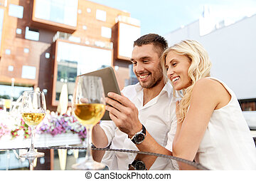 happy couple with tablet pc at restaurant terrace - love,...