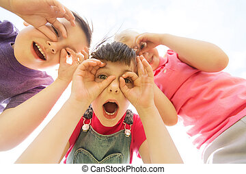 group of kids having fun and making faces outdoors - summer,...