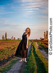 Girl in black dress is dancing on the field road barefoot. happy woman outdoors. Sunset. meadow.