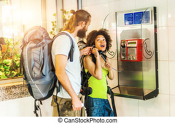 Couple on pay phone laughing
