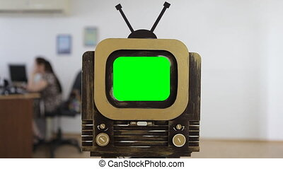 Vintage retro TV with a green screen at office background.