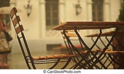 Slow motion video of street cafe tables and woman with...