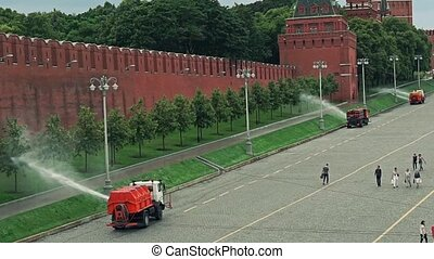 Watering machines in action near Moscow Kremlin wall. Slow...