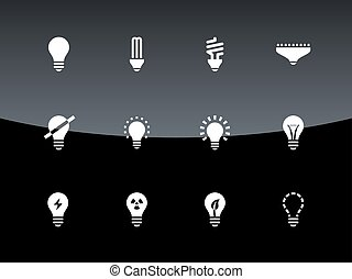 Light bulb and CFL lamp icons on black background.