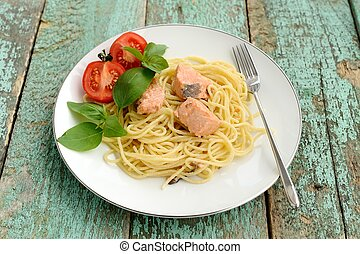 Pasta with tomatoes, green basil and salmon filet in white plate
