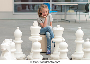 Little girl playing outdoor chess game.