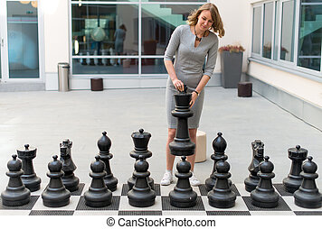 Woman playing outdoor chess game.