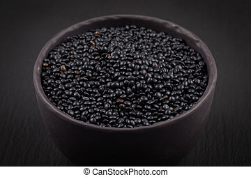 many black beluga lentil seeds in small dark bowl cup...