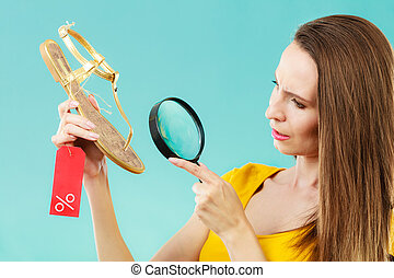 woman choosing shoes searching through magnifying glass -...