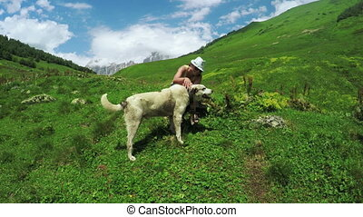 Dog in alpine meadows with girl - Camera on steadicam moves...