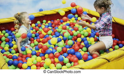 children playing in the ball pool - cheerful kids playing in...