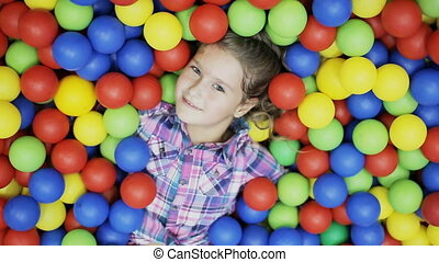 little girl is in the ball pool - cheerful kid in ball pool