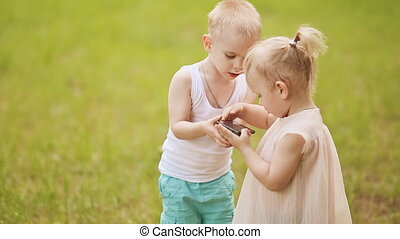 Cute baby girl and boy play with mobile phone