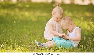 Cute baby girl and boy play with phone