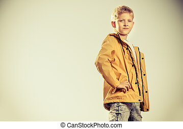 yellow rain coat - Cool modern eight-year boy posing on a...