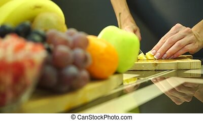 Female hands cutting an orange for a fruit salad - Slow...
