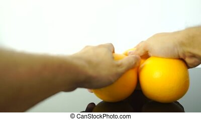 Three oranges being placed on a reflecting table, 2 videos...