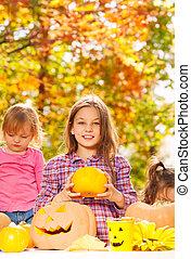 Sisters cave Halloween pumpkins in the garden