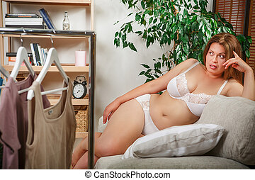 Woman trying dresses at home - Fat woman luing on sofa or...