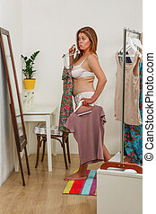 Woman trying dresses at home - Beautiful fat woman in...