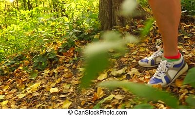 Girl walking along autumn road covered with fallen leaves -...