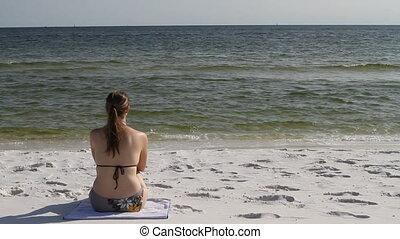Woman Sitting At Beach In Bikini