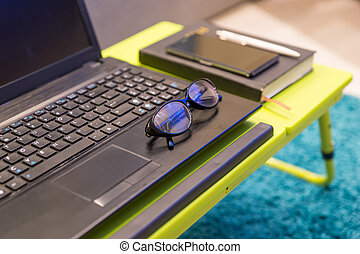 Neat tabletop workstation with eyeglasses lying on the...