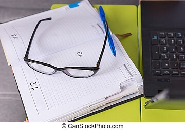 Pair of glasses and a pen on a journal lying on the laptop...