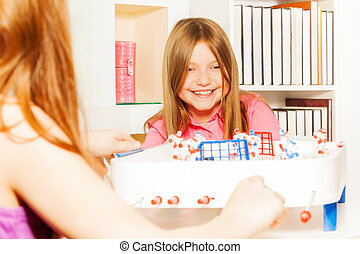 Girl playing table board hockey with her friend - Happy girl...