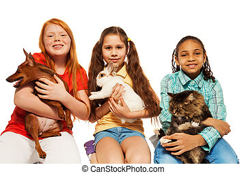 Diverse girls playing with their pets together, hugging cat,...