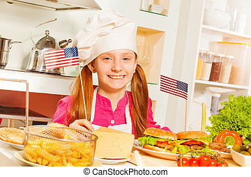 Happy girl in cook uniform preparing American food