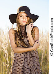 Beautiful young lady model posing in front of camera in a field at sunrise