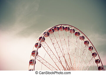 Vintage style Ferris wheel with blue sky background