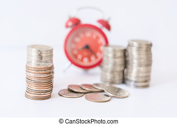 selective focus on coins front of blur red alarm clock,...