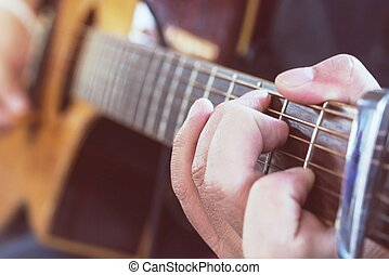 Practicing in playing guitar, Hand of young men playing guitar chord C, selective focus on finger