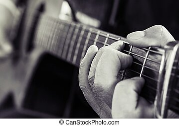 Practicing in playing guitar, Hand of young men playing guitar chord C, selective focus on finger, black and white style