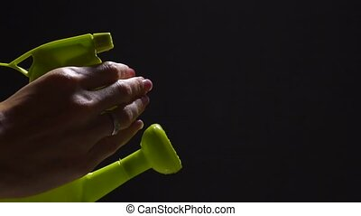 Green watering can with pulverizer and female hand, slow...