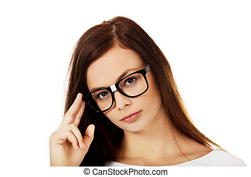 Young woman holding her glasses