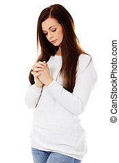 Beautiful young caucasian woman praying.