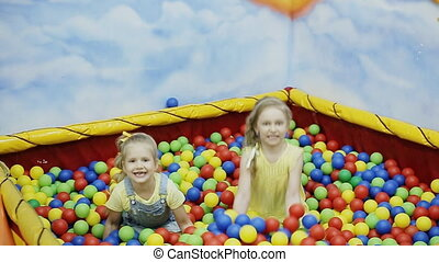 Children throw the balls in ball pool. slow motion
