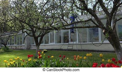 male worker washing greenhouse in beautiful garden.