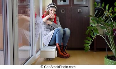 Hot woman undress cap and scarf sitting on radiator. Temperature rising.