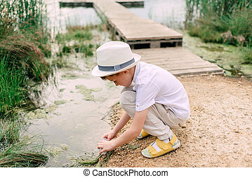 boy in straw hat near the river