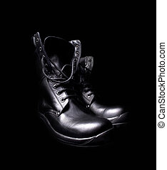 a pair of black leather military boots on black background