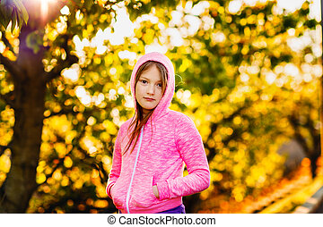 Outdoor portrait of a cute little girl of 8-9 years old at...