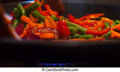 Frying and mixing vegetables close up video